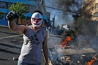 A masked demonstrator raises his clenched fist at a burning barricade during protests in Valparaiso, Chile, on October 20, 2019. - Fresh clashes broke out in Chile's capital Santiago on Sunday after two people died when a supermarket was torched overnight as violent protests sparked by anger over economic conditions and social inequality raged into a third day. (Photo by JAVIER TORRES / AFP)