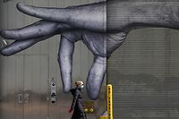 (FILES) In this file photo taken on April 22, 2020 a woman in a mask walks past a mural of a hand on the side of a building in Midtown New York City  April 22, 2020. - The United States recorded its 10 millionth case of the coronavirus Monday, according to a count by Johns Hopkins University, the same day that Pfizer and BioNTech announced their vaccine showed 90 percent effectiveness. Shortly before 1400 GMT on November 9, 2020 the tracker by the Baltimore-based university showed 10,018,278 cases recorded in the US since the pandemic began, and 237,742 deaths. Both are the highest tolls in absolute terms in the world. (Photo by TIMOTHY A. CLARY / AFP)
