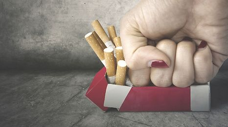 Concept of Quit smoking. Image of a woman fist crushing a pack of cigarettes on the floor