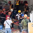 Rescue workers carry a survivor out of the collapsed Chuzon supermarket in Porac, pampanga province on April 23, 2019, a day after a 6.3 magnitude quake. - Philippine rescuers were scrambling April 23 to reach dozens of people feared buried under a building near Manila that collapsed a day earlier in a powerful earthquake, as the death toll climbed to 11. (Photo by Noel CELIS / AFP)