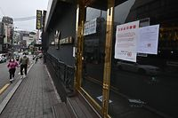A couple wearing face masks walk past a night club, now closed following a visit by a confirmed COVID-19 coronavirus coronavirus patient, in the popular nightlife district of Itaewon in Seoul on May 10, 2020. - South Korea's capital has ordered the closure of all clubs and bars after a burst of new cases sparked fears of a second coronavirus wave as President Moon Jae-in urged the public to remain vigilant. (Photo by Jung Yeon-je / AFP)
