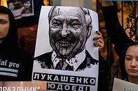 TOPSHOT - Demonstrators with a placard with an image of Belarus' President Alexander Lukashenko protest against the results of Belarusian presidential election outside the Belarusian embassy in Moscow on August 12, 2020. (Photo by Dimitar DILKOFF / AFP)
