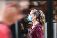 """A woman wearing a protective mask walks on a street in Lille, northern France, on July 30, 2020, as The Nord Prefecture announced, the reinforcement of the health measures at a local level to attempt to halt the rising cases of coronavirus Covid-19, which have been seen in the region during the past two weeks. - In a discussion between the French Health Minister, The Nord Prefet and Nord Regional Health Agency director (ARS) on July 29, the possibility of making the wearing of protective masks compulsory outside """"due to the proximity with Belgium"""" was spoken of in an effort to halt the rise of coronavirus cases"""