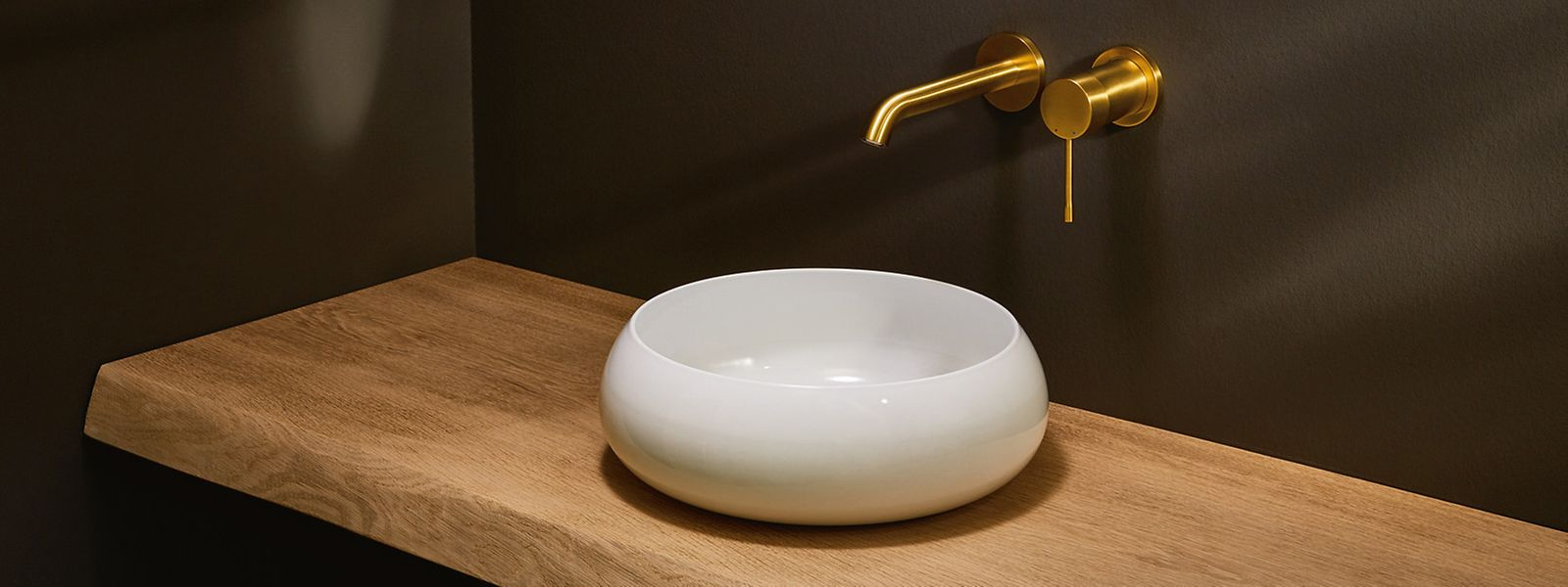 Mit goldenen Armaturen tun sich viele noch schwer - aber sie sind ein Trend für Badezimmer. Gut wirken sie zum Beispiel in einem dunkel gehaltenenUmfeld.