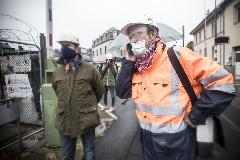 Mit Masken und Regenschirmen ausgestattet, protestierten etwa 15 Personen am Donnerstag vor Ort.