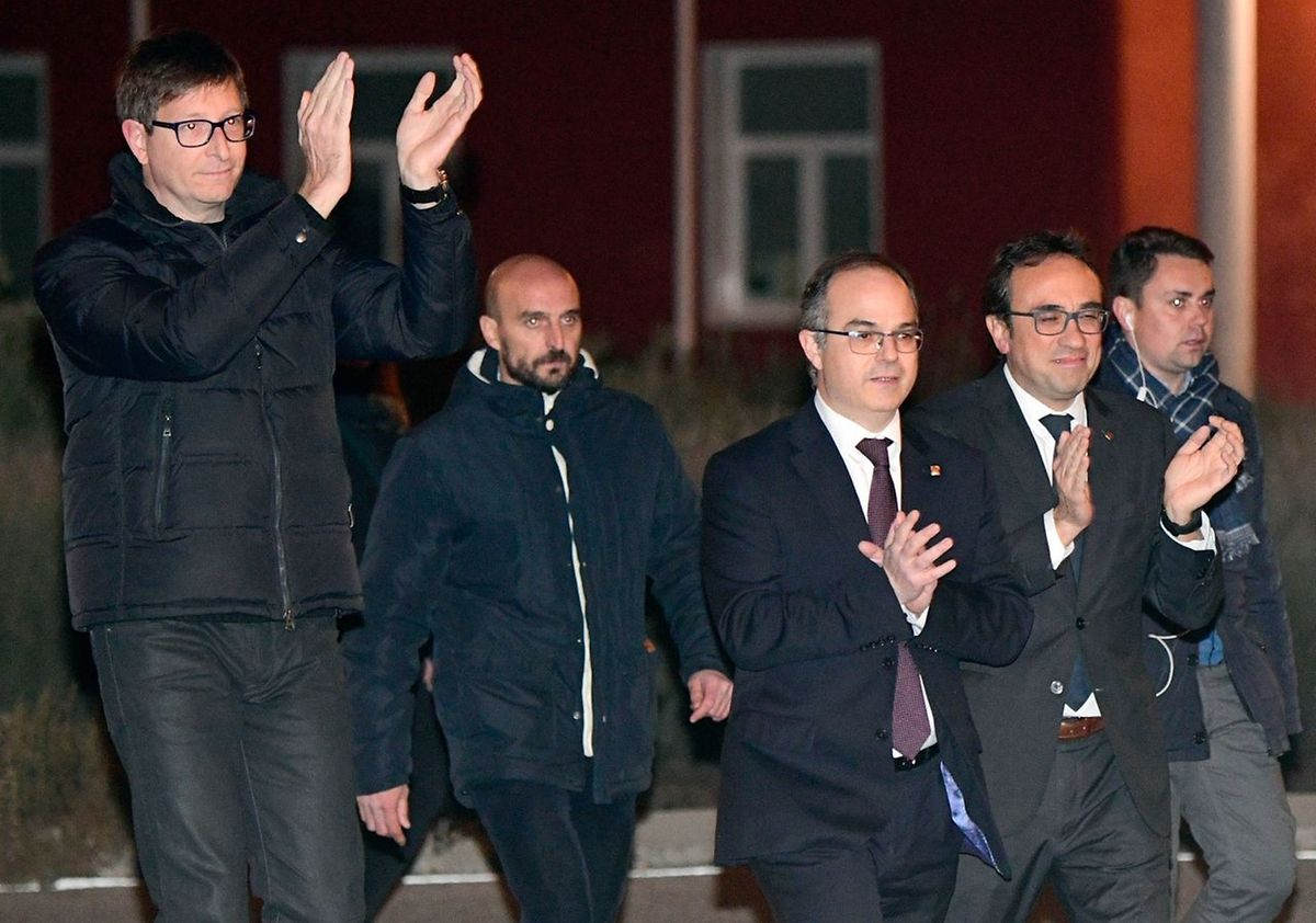 Deposed Catalan regional government justice chief, Carles Mundo (L) , Deposed Catalan regional government spokesperson Jordi Turull (3L) and Deposed Catalan regional government Territory and Sustainability chief Josep Rull (2R) applaud as they leave the Estremera prison, some 80km east of Madrid, on December 4, 2017. Six former Catalan ministers who were remanded in custody last month were released on bail of 100,000 euros ($120,000) each as an investigation into charges of rebellion, sedition and misuse of public funds continues. / AFP PHOTO / PIERRE-PHILIPPE MARCOU