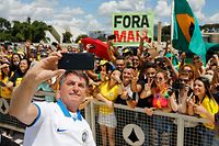 TOPSHOT - Brazilian President Jair Bolsonaro takes a selfie with supporters in front of the Planalto Palace, after a protest against the National Congress and the Supreme Court, in Brasilia, on March 15, 2020. (Photo by Sergio LIMA / AFP)