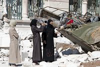 "Syrian women stand next to a woman taking a picture of a child playing on a destroyed tank outside a mosque that was destroyed during fighting between Syrian rebels and regime forces in the northern city of Azaz on September 23, 2012. Regime aircraft hammered insurgent bastions nationwide as rebels said they now control most of the country and have moved their command centre from Turkey to ""liberated areas"" inside Syria. AFP PHOTO/MIGUEL MEDINA"