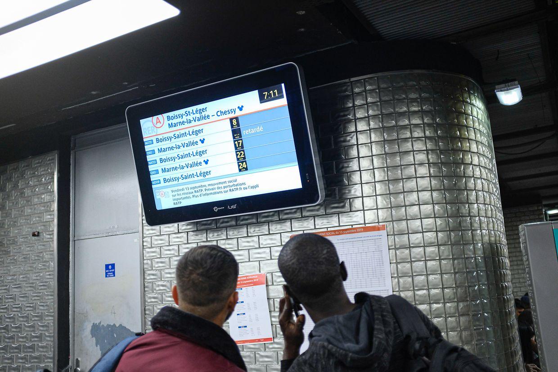 Paris: Zwei Männer stehen in einer Metrostation vor einem Monitor, der die Ankunfts- und Abfahrtzeiten anzeigt.
