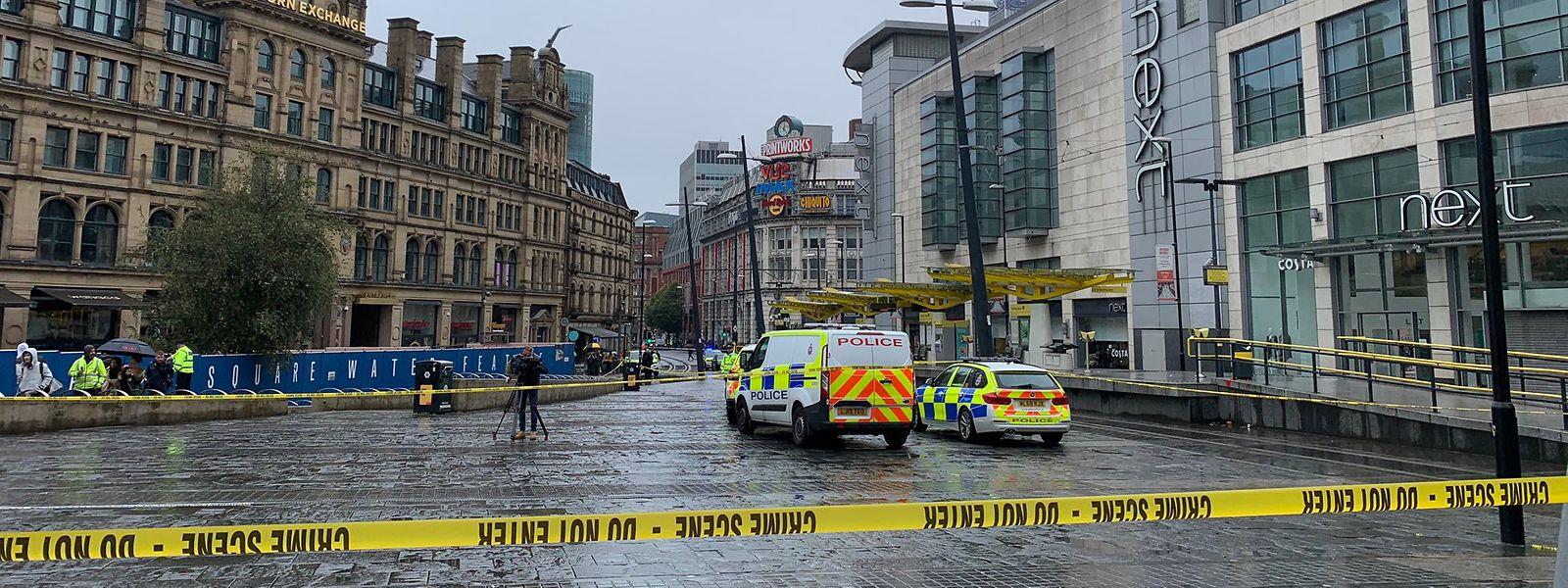 Manchester: Der Tatort ist mit Absperrband abgesperrt, Polizeifahrzeuge stehen daneben. In Manchester sind bei einem Messerangriff ersten Ermittlungen zufolge mehrere Menschen verletzt worden.