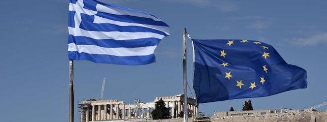 Les drapeaux grec et européen flottent devant l'ancienne acropole d'Athènes.