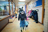08.02.2021, Niederlande, Den Haag: Ein Kind kommt in eine Grundschule. Eigentlich sollte dies nach dem Lockdown für alle Grundschüler der erste Schultag sein. Doch viele Grundschulen mussten aufgrund des Wintereinbruchs geschlossen bleiben. Foto: Bart Maat/ANP/dpa +++ dpa-Bildfunk +++