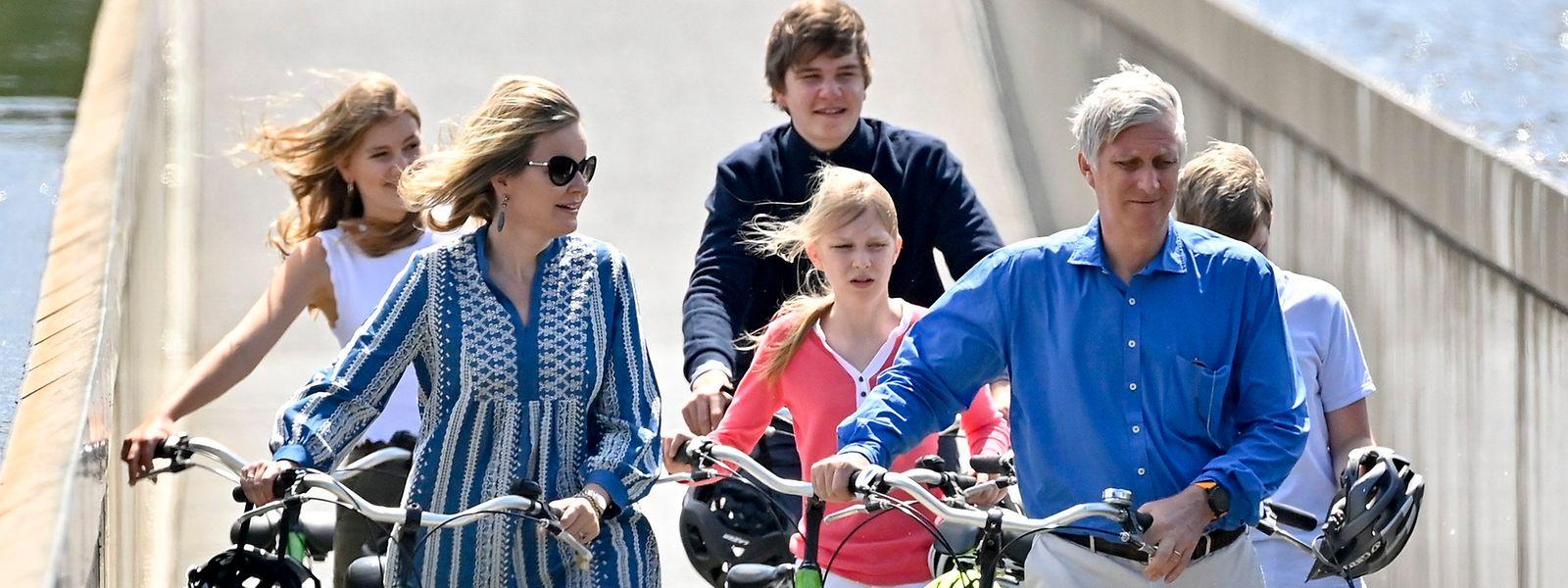 Die belgische Königsfamilie, Kronprinzessin Elisabeth (l-r), Königin Mathilde, Prinz Gabriel, Prinzessin Eleonore, König Philippe und Prinz Emmanuel, schieben ihre Fahrräder während ihres Besuchs im Bokrijk-Park über einen Radweg, der mitten durch einen See geht.