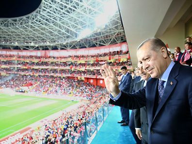 "This handout photo taken and released on March 24, 2017 by the Turkish Presidential Press Service shows Turkey's President Recep Tayyip Erdogan greeting supporters during the Fifa World Cup 2018 qualification football match between Turkey and Finland at Antalya arena stadium in Antalya. / AFP PHOTO / TURKISH PRESIDENCY PRESS OFFICE / KAYHAN OZER / RESTRICTED TO EDITORIAL USE - MANDATORY CREDIT ""AFP PHOTO / TURKISH PPRESIDENTIAL PRESS OFFICE / KAYHAN OZER"" - NO MARKETING NO ADVERTISING CAMPAIGNS - DISTRIBUTED AS A SERVICE TO CLIENTS"
