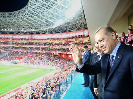 """This handout photo taken and released on March 24, 2017 by the Turkish Presidential Press Service shows Turkey's President Recep Tayyip Erdogan greeting supporters during the Fifa World Cup 2018 qualification football match between Turkey and Finland at Antalya arena stadium in Antalya. / AFP PHOTO / TURKISH PRESIDENCY PRESS OFFICE / KAYHAN OZER / RESTRICTED TO EDITORIAL USE - MANDATORY CREDIT """"AFP PHOTO / TURKISH PPRESIDENTIAL PRESS OFFICE / KAYHAN OZER"""" - NO MARKETING NO ADVERTISING CAMPAIGNS - DISTRIBUTED AS A SERVICE TO CLIENTS"""