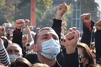 Wearing protective mouth and nose masks people protest during a rally against the country's agreement to end fighting with Azerbaijan over the disputed Nagorno-Karabakh region outside the government headquarters in Yerevan on November 11, 2020. - More than 2,000 demonstrators protested in the Armenian capital as anger mounted over Prime Minister Nikol Pashinyan's decision to cede swathes of disputed territory to Azerbaijan under a controversial peace deal. (Photo by Karen MINASYAN / AFP)