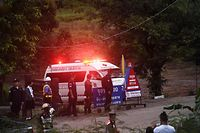 TOPSHOT - An ambulance leaves the Tham Luang cave area after divers evacuated some of the 12 boys and their coach trapped at the cave in Khun Nam Nang Non Forest Park in the Mae Sai district of Chiang Rai province on July 8, 2018. Elite divers on July 8 began the extremely dangerous operation to extract 12 boys and their football coach who have been trapped in a flooded cave complex in northern Thailand for more than two weeks, as looming monsoon rains threatened the rescue effort. / AFP PHOTO / LILLIAN SUWANRUMPHA
