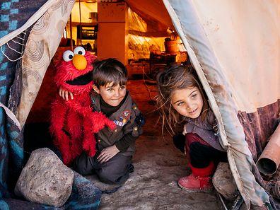 """Fotograf Ryan Heffernan fing die Augenblicke ein, in denen Kinder auf die Puppe """"Elmo"""" trafen. Die Bilder entstanden imjordanischen Zaatari-Lager, in dem über 80000 Flüchtlinge leben."""
