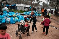 A boy pushes another one in a cart as they play in the overcrowded Moria camp on the island of Lesbos on March 7, 2020. - Over 1,700 migrants have landed on Lesbos and four other Aegean islands from Turkey over the past week, adding to the 38,000 already crammed into abysmal and overstretched refugee centres. (Photo by LOUISA GOULIAMAKI / AFP)