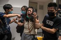 TOPSHOT - A woman reacts after she was hit with pepper spray deployed by police as they cleared a street with protesters rallying against a new national security law in Hong Kong on July 1, 2020, on the 23rd anniversary of the city's handover from Britain to China. - A man found in possession of a Hong Kong independence flag became the first person to be arrested under Beijing's new national security law for the city, police said on July 1. (Photo by DALE DE LA REY / AFP)