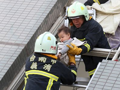 Rescue workers remove a baby from the site where a 17-storey apartment building collapsed after an earthquake hit Taiwan.