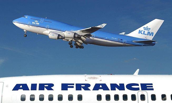 A KLM plane flying over an Air France place at Schipol Airport in Amsterdam, Netherlands