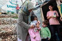 Uma mulher coloca uma máscara numa criança, num campo de refugiados na ilha grega de Lesbos.