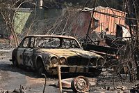 "A vintage Jaguar car sits in ruins after a bushfire destroyed a property in Old Bar, 350km north of Sydney on November 10, 2019. - Firefighters in eastern Australia were on November 10 assessing damage from ferocious bushfires that have devastated communities and rushing to prepare for ""bad, if not worse"" conditions expected to flare in the coming days. (Photo by PETER PARKS / AFP)"