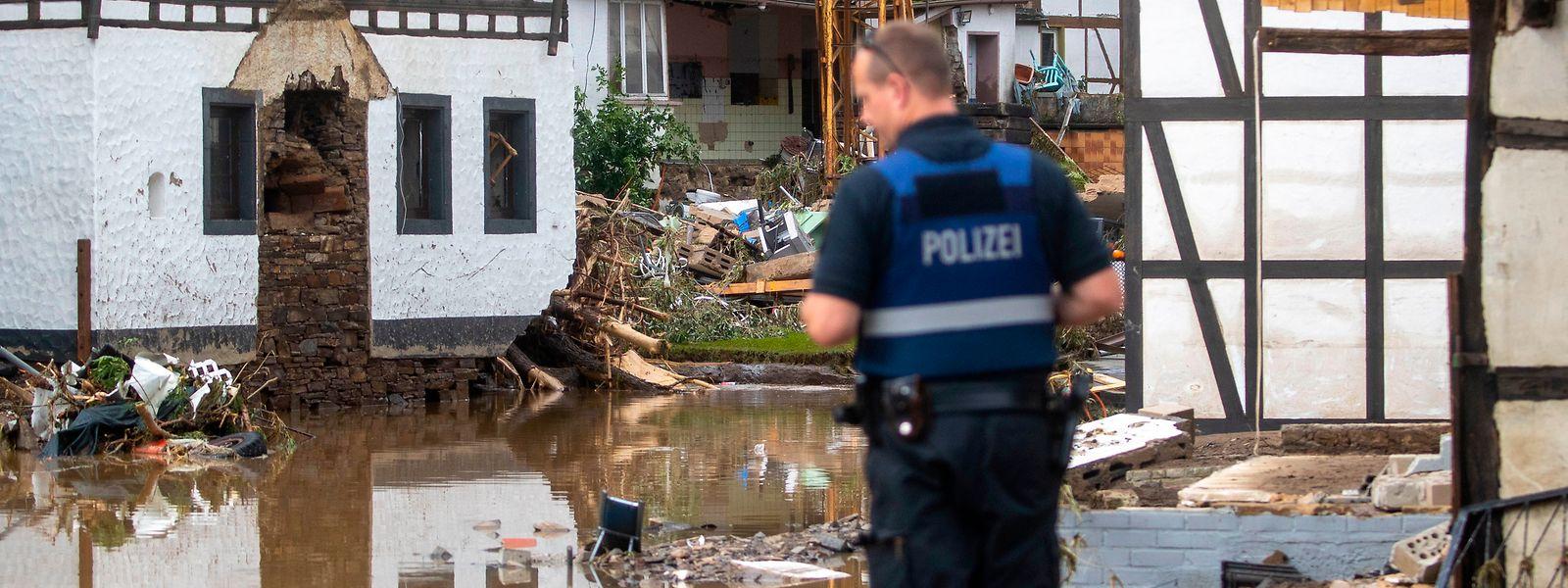 Ein Polizist verschafft sich in dem Ort im Kreis Ahrweiler nach dem Unwetter und den Überschwemmungen einen Überblick.