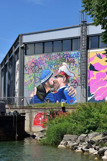 Graffiti-Artist küsst Polizist: eine Gemeinschaftsproduktion im Hafengebiet von Karikaturist Gerhard Haderer und Streetartist SHED.