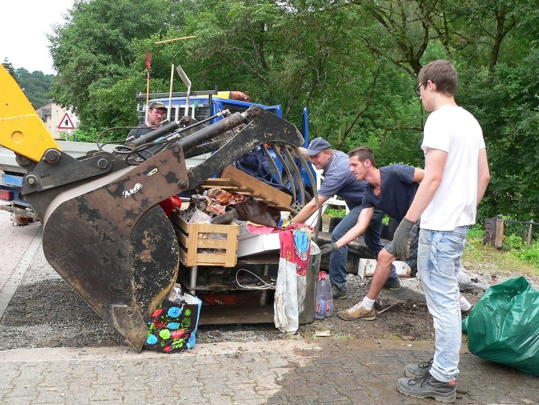 Die Menschen der Gemeinde helfen bei den Aufräumarbeiten.
