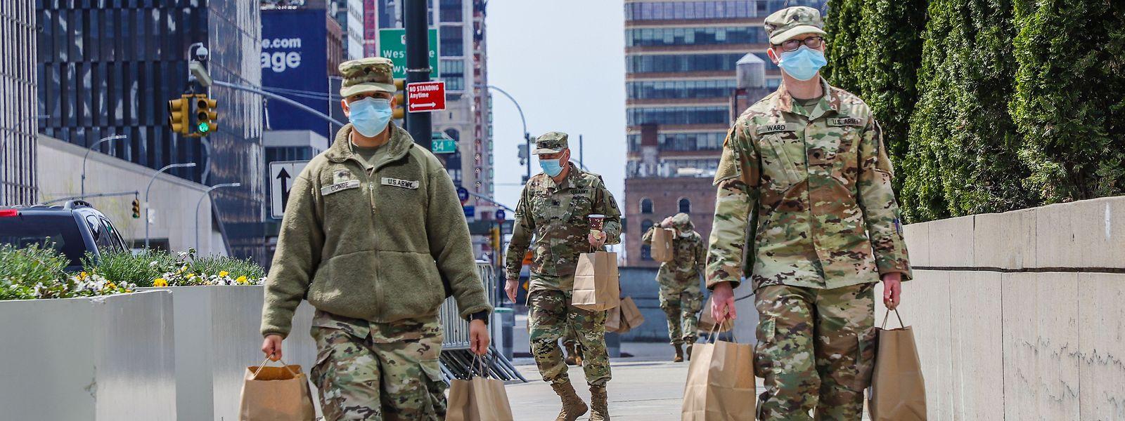 Soldados norte-americanos carregam sacos em frente ao Centro de Exposições Jacob K. Javits, em Nova Iorque, onde foi instalado um hospital temporário.