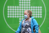 A woman wearing a face mask or covering due to the COVID-19 pandemic, walks past a sign for a pharmacy in Liverpool, north west England on October 2, 2020, following the  announcement of new local restrictions for certain areas in the northwest of the country, due to a resurgence of novel coronavirus cases. - The British government on Thursday extended lockdowns to Liverpool and several other towns in northern England, effectively putting more than a quarter of the country under tighter coronavirus restrictions. Health Secretary Matt Hancock said limits on social gatherings would be extended to the Liverpool City region, which has a population of about 1.5 million. (Photo by Oli SCARFF / AFP)