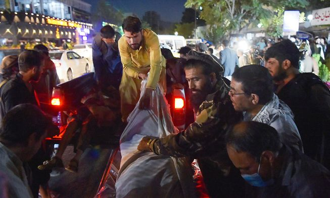 Volunteers and medical staff unload bodies from a pickup truck outside a hospital after two explosions outside the airport in Kabul