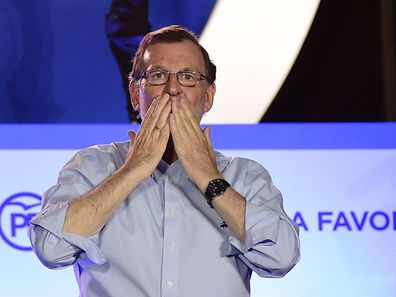 Leader of the Popular Party (PP) and Spain's caretaker Prime Minister Mariano Rajoy blows kisses to his supporters at the PP headquarters during Spain's general election in Madrid on June 26, 2016.