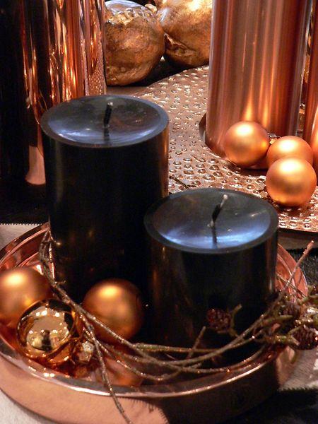 Schwarze Kerzen kombiniert mit kupferfarbenen Deko-Elementen sind eine ausgefallene und trendige Idee für die Adventszeit.