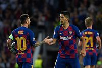 Barcelona's Uruguayan forward Luis Suarez (R) is congratulated by teammate Barcelona's Argentine forward Lionel Messi after scoring a goal during the UEFA Champions League Group F football match between Barcelona and Inter Milan at the Camp Nou stadium in Barcelona, on October 2, 2019. (Photo by LLUIS GENE / AFP)