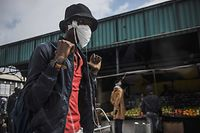 A young man wears a home made mask as a preventive measure as he walks through the busy Wanderers taxi rank in Johannesburg, on March 18, 2020. - African countries have been among the last to be hit by the global COVID-19 coronavirus epidemic but as cases rise, many nations are now taking strict measures to block the deadly illness. (Photo by MARCO LONGARI / AFP)