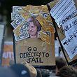 Des manifestants brandissent des panneaux lors d'un mouvement de protestation anti-conservateurs du DUP, Democratic Unionist Party (parti unioniste démocratique) dans Downing Street, où se trouve le cabinet de la Première ministre conservatrice Theresa May, à Londres.