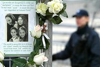 A Belgian police officer stands next to a poster showing pictures of (above, L to R) An Marchal, Eefje Lambrecks, (below, L to R) Julie Lejeune and Melissa Russo, the victims of convicted child rapist Marc Dutroux, outside the Arlon courthouse, southeast Belgium March 8, 2004. Belgian Examining Magistrate Jacques Langlois, who completed the investigation into the crimes allegedly committed by Dutroux, will testify today before the court where Dutroux stand trial with his ex-wife Michelle Martin, Michel Lelievre and Michel Nihoul, for the abduction and rape of six girls and the murder of four of them in the mid-1990s.    REUTERS/Yves Herman
