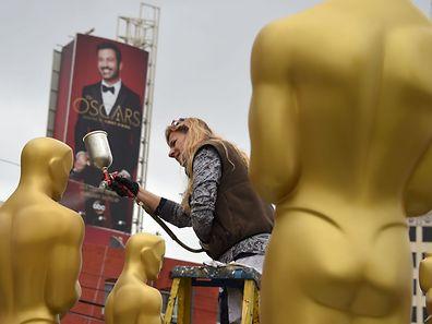 Dena D'Angelo peint les fameuses statues  avant la grande cérémonie que présentera l'animateur Jimmy Kimmel (en toile de fond).
