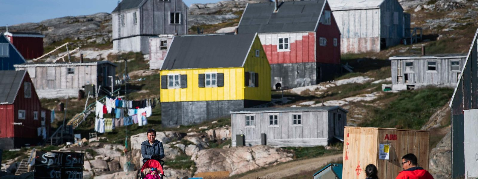 Residents of Kulusuk walk in Kulusuk, Greenland on August 16, 2019. - Greenland is not for sale, the mineral-rich island said on August 16, 2019, after a newspaper reported that US President Donald Trump was asking advisers whether it's possible for the United States to buy the Arctic island. (Photo by Jonathan NACKSTRAND / AFP)