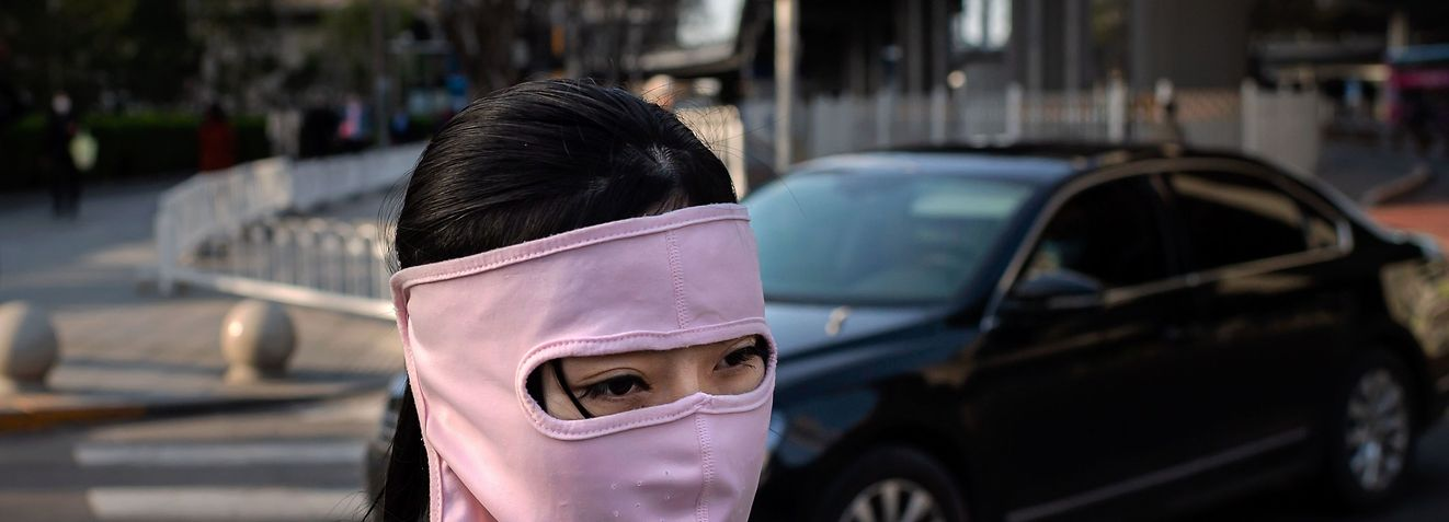 A woman wearing a face mask amid the COVID-19 coronavirus outbreak walks outside office buildings in Beijing on April 1, 2020. (Photo by NICOLAS ASFOURI / AFP)