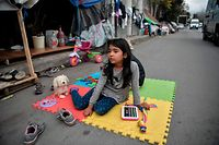 An Afghan child plays on a street by her family's tent outside Eleonas refugee camp in Athens, on November 20, 2019. - Some 14 Afghan refugees, including families with children, live outside the camp in tents, without any facilities. Greece will shut down its largest three migrant camps on islands facing Turkey, and replace them with new stricter facilities for identification, relocation and deportation, officials said on November 20. (Photo by LOUISA GOULIAMAKI / AFP)