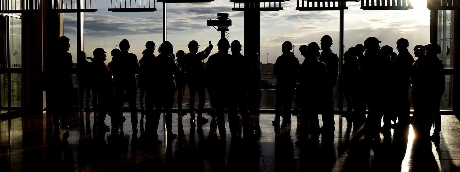 Besucher der Baustelle des Hauptstadtflughafens BER stehen im Hauptterminal und schauen auf das Rollfeld.