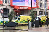 11.10.2019, Großbritannien, Manchester: Rettungsfahrzeuge und bewaffnete Polizeibeamte stehen vor einem Eingang eines Einkaufszentrums. In Manchester sind bei einem Messerangriff ersten Ermittlungen zufolge mehrere Menschen verletzt worden. Foto: Peter Byrne/PA Wire/dpa +++ dpa-Bildfunk +++