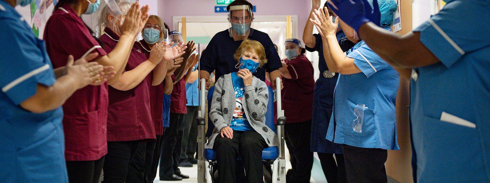 Die 90-jährige Margaret Keenan (M) wird im Universitätskrankenhaus Coventry von Mitarbeitern des Gesundheitswesens applaudiert, als sie auf ihre Station zurückkehrt, nachdem sie zu Beginn der Impfkampagne als erste Person im Vereinigten Königreich den Pfizer/BioNtech-Impfstoff gegen das neuartige Coronavirus erhalten hat.