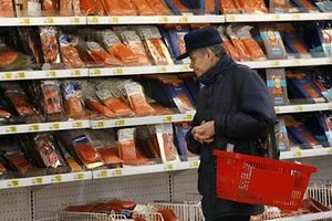 A customer stands in front of shelves at the fish department of a hypermarket of French grocery retailer Auchan in Moscow, January 15, 2015. For millions of pensioners who make up about a third of Russia's population, rising prices are spurring anger over declining living standards, threatening a pool of support President Vladimir Putin cannot afford to lose. Picture taken January 15, 2015. To match story RUSSIA-CRISIS/PENSIONERS    REUTERS/Maxim Zmeyev (RUSSIA - Tags: BUSINESS FOOD POLITICS SOCIETY)