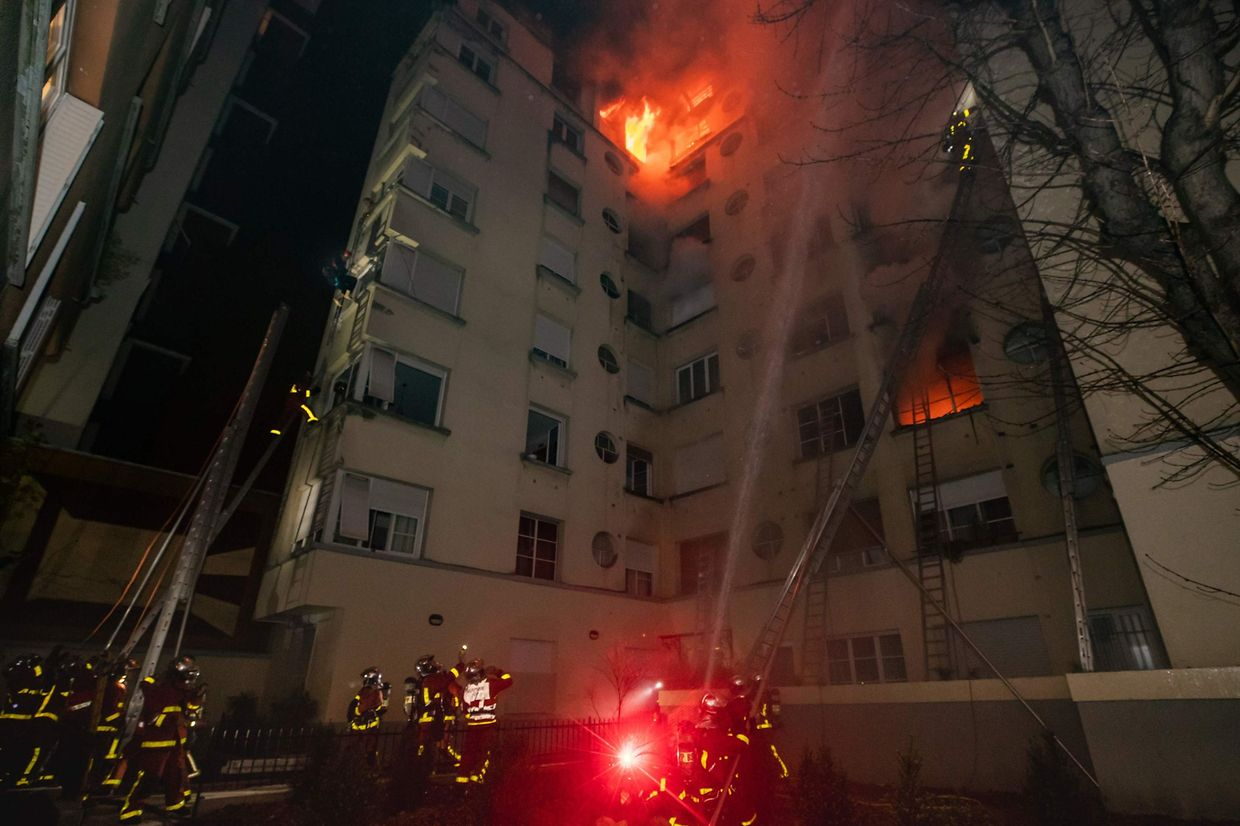 """This handout picture taken and released by the Paris firefighters brigade in the night of February 5, 2019 shows firemen spraying water as a fire burns in a building in Erlanger street in the 16th arrondissement in Paris. - A woman has been arrested over a deadly blaze that killed eight people in Paris and police are treating the fire as a possible arson attack, a prosecutor said early on February 5. (Photo by HO / BSPP - Brigade de sapeurs-pompiers de Paris / AFP) / RESTRICTED TO EDITORIAL USE - MANDATORY CREDIT """"AFP PHOTO / BSPP"""" - NO MARKETING NO ADVERTISING CAMPAIGNS - DISTRIBUTED AS A SERVICE TO CLIENTS ---"""