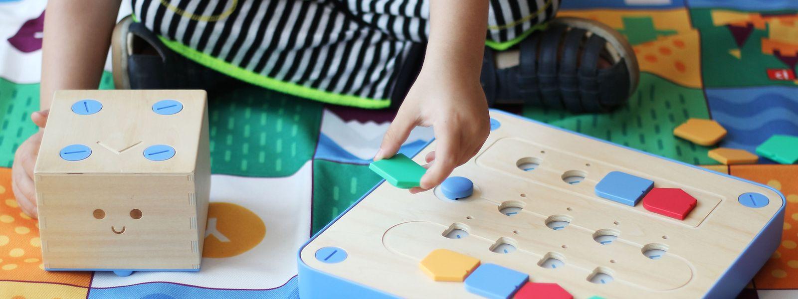 Der Cubetto ist ein Holzroboter mit Rollen. Er lässt sich mit bunten Bausteinen auf dem Bedienfeld steuern. Jede Farbe steht für eine andere Bewegung, die der Roboter ausführen soll.